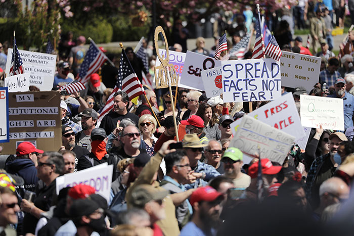Demonstrators crowd together at a protest opposing Washington state's stay-home order to slow the coronavirus outbreak Sunday, April 19, 2020, in Olympia, Wash. Washington Gov. Jay Inslee has blasted President Donald Trump's calls to