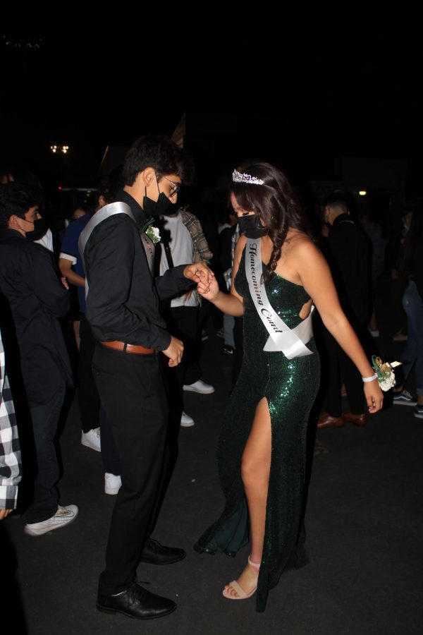 Homecoming Princess Daisy Razon and Prince Joshua Robles wearing their masks while on the dance floor